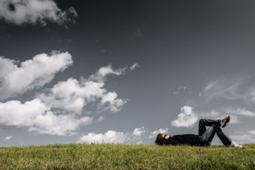 man lying in grass staring up at clouds